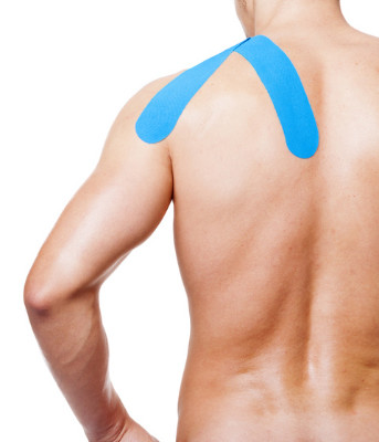 Muscular man with kinesiotaping on the shoulder, isolated on white